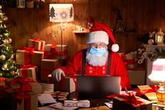 Santa wearing face mask holding Christmas gift on xmas eve using laptop.