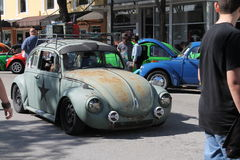 Old beat up car driving. Classic VW Bug driving on road. outdoors on a sunny day Stock Photos
