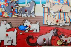 Old, beat - up child`s wood puzzle of playful pups and kittens. Nostalgic toy, depicting a child`s well - worn wooden puzzle, with pieces of playful pups and royalty free stock photography