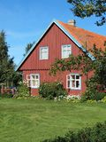 Old beautiful home in village, Lithuania. Old red wooden home and garden in village Minge in summer , Lithuania stock photo