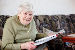 Old beautiful senior woman of 85 years reading book, indoors Royalty Free Stock Image