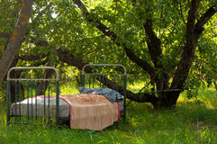 An old bed in the garden. This old bed stands in the shade of garden trees, a perfect place for a nap stock images
