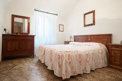 Old bedroom with queen size bed in ancient house. Old bedroom with queen size bed in ancient italian house stock photo