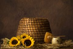 Old beehive and sunflowers stock images