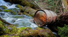 Old Beer Keg in the River. Old bullet riddled  rusty beer keg sits in the slow exposure waterfall Stock Photos
