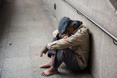 Old beggar or Homeless man in town. Old beggar or Homeless dirty man without shoes sitting and sleeping on walkway of modern city. feeling tired and hungry with Royalty Free Stock Images