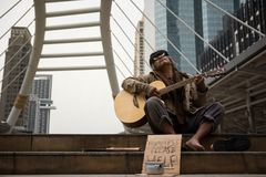 Old beggar sing and play guitar royalty free stock photo