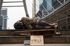 Beggar or Homeless man sleep in city at winter. Old beggar or Homeless dirty man sleeping on stair of modern city with guitar, donate bowl, paper cardboard with royalty free stock photo