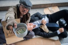 Beggar with drunk Businessman in city. Old beggar or homeless senior guy raise donated bowl to ask for money while drunk Business men or Buinessman holding beer Stock Images