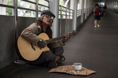 Old beggar play guitar to beg money. Old beggar or Homeless dirty man singing and playing guitar on footpath of modern city with donate bowl, paper cardboard Stock Photo