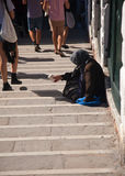 Old begging lady on steps Royalty Free Stock Photo