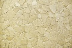 Old beige mosaic stone wall background texture. Close up Royalty Free Stock Photo