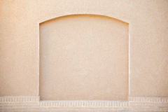 Old beige stucco wall with decorated arch Stock Images