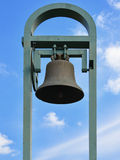 An old bell abandoned its support backed by metal background blue sky with passing clouds.  Stock Images
