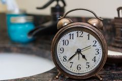 Old bell alarm clock in a bathroom at early hour, getting ready Stock Image