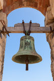 Old bell hanging in stone arch. Ancient fortress of Calafell town, Spain Stock Image