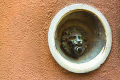 Old bell system in shape of lion on colored plaster Stock Photo