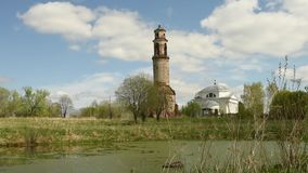the old bell tower and the temple by the pond under the shadows of clouds stock video