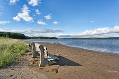 Old bench on beach with river in background Royalty Free Stock Photography