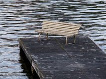 Old bench on a dock in water Royalty Free Stock Photo