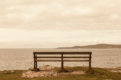 Old bench facing an open view with sea and mountains. Stock Images