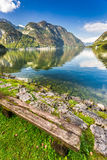 Old bench at mountain lake in the Alps Royalty Free Stock Photo