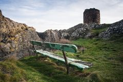 Old bench on soft grass near the rocks and ancient tower i Scotland. Old green painted bench on soft grass near the rocks and ancient tower i Scotland stock image