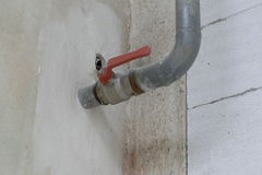 Old bent tube with a red tap Stock Images