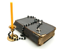 Old Bible. With  candle in  bronze candlestick, cross and beads on white background Stock Image