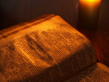 Old bible by candlelight. Open bible text by candlelight Royalty Free Stock Images