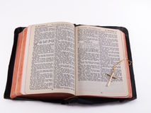 Old Bible with gold cross. KJV Bible opened to Matthew 28, with gold cross on chain, isolated with clipping path Stock Images