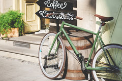 Old bicycle against coffeehouse on sunny day Stock Images