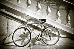 Old bicycle against a marble wall Royalty Free Stock Image