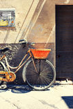 Old bicycle with a basket against the wall advertisement in Italy Stock Photos