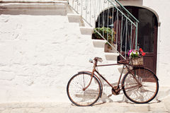 Old bicycle with a basket. Beautiful old bicycle with a basket against a wall in Italy Royalty Free Stock Photography