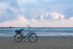 Old bicycle on the beach at sunset with storm sea and foam waves background. Old bicycle on the beach at sunset with storm sea and foam waves background stock photography