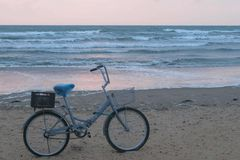 Old bicycle on the beach at sunset with storm sea and foam waves background. Old bicycle on the beach at sunset with storm sea and foam waves background stock photo