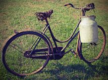 Old bicycle with a broken saddle and the milk can milkman. With vintage effect Stock Photos