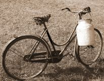 Very old bicycle with a broken saddle and the milk can milkman. Old bicycle with a broken saddle and the milk can milkman with sepia tone effect Stock Photo