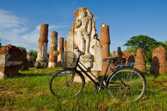 Old bicycle and  buddha statue Royalty Free Stock Photography