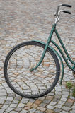 Old bicycle. An old green bike parked in a cobblestone pavement Stock Photography