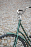 Old bicycle. An old green bike parked in a cobblestone pavement Stock Photos