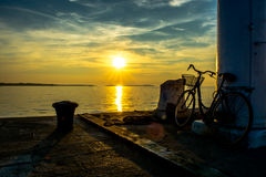 Old Bicycle on Jetty at Sunset Stock Photo