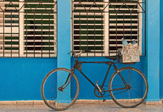 Old bicycle leaning against barred,shuttered windows and blue wall Royalty Free Stock Photo