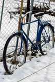 Old Bicycle leaning against the fence in winter royalty free stock photos