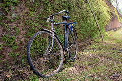 An old bicycle leaning against one of the old brick walls of the Stock Images