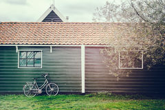 Old bicycle leaning against wooden barn Stock Photo