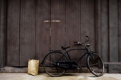 Old bicycle leaning against old wooden doors. With a brown paper stock images