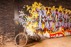 Old bicycle is leaning on art graffiti wall,798 street, Beijing on 25 May 2013. Art graffiti in Beijing Dashanzi Art District which houses an artistic community Stock Photos
