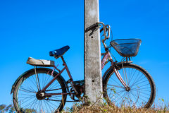 Old bicycle leaning on the electric pole and blue sky.  royalty free stock images